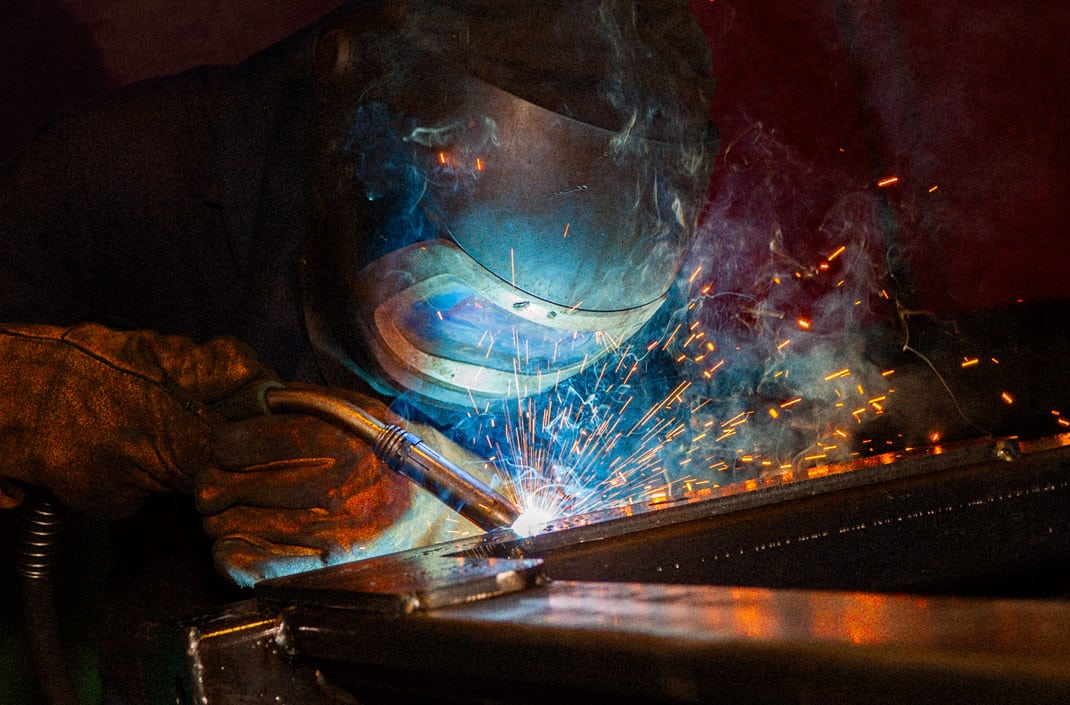 On site industrial photography of manufacturing process. GMAW welder working on a commercial trailer chassis. Images for use online and for sales material.