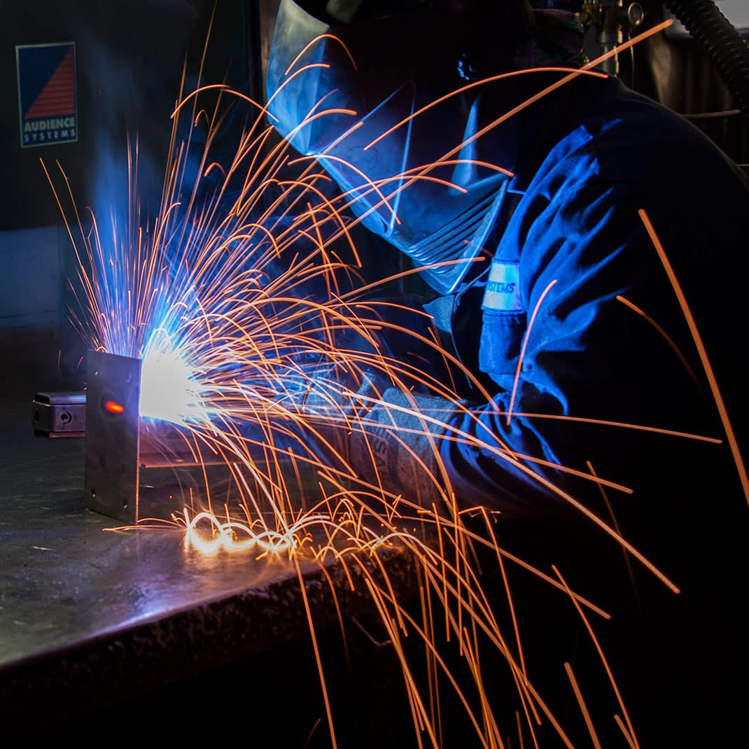 Sparks fly as this MIG welder works on a bespoke audience seating project. Photographer Toby Smedley on location at the Audience Systems factory in Westbury. Images used for print and web.